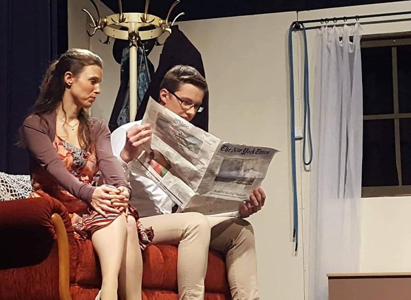 """Szene aus dem Theaterstück """"Arsenic and Old Lace"""": Ein Paar schaut in die Zeitung"""